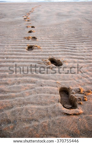 Footprints in the sand of a beach with grooves during a sunset in Mazagon, province of Huelva, Spain - stock photo