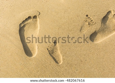 footprints in the sand of boy and father.