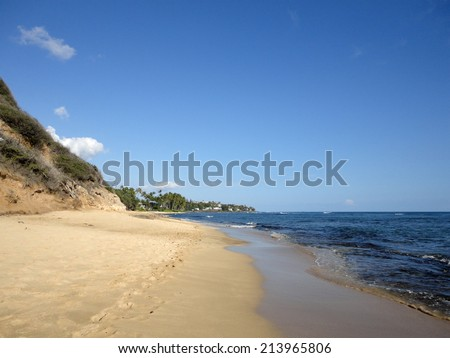 Footprints in the sand on empty Diamond Head Beach on a Beautiful day with vegetation on cliff side and nice house in the distance on Oahu, Hawaii. - stock photo