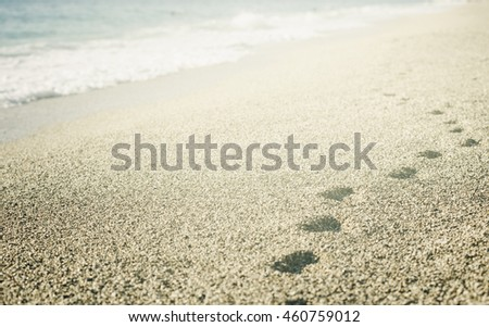 Footprints in the sand on the beach.
