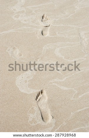 Footprints in the sand on the beach- texture and background