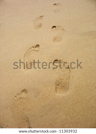 Footprints in the sand on the beach.  This can be used for a wide range of concepts. - stock photo
