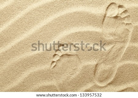 Footprints in the sand waves as background - stock photo