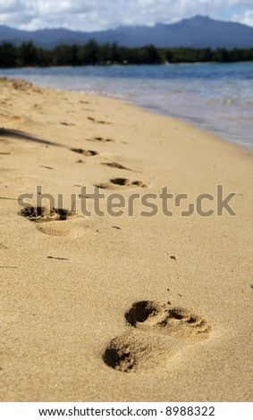 footprints in the sand with blue water and distant mountains
