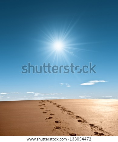 Footprints in the sand with bright sunshine - stock photo