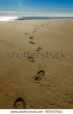 Footprints lead off to the ocean on a beach in New England.