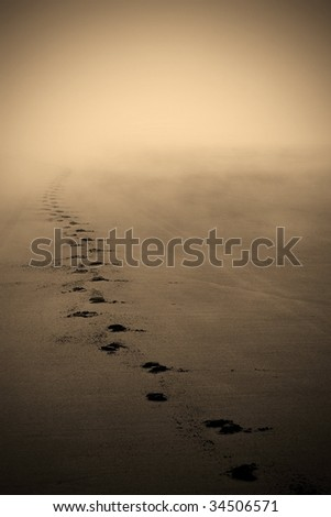 Footprints leading off into misty horizon. - stock photo