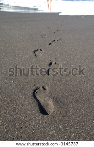 Footprints leading to the sea. - stock photo