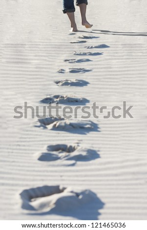 Footprints of a girl walking on the sand at the beach - stock photo