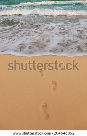 footprints on a sandy beach and the sea - stock photo