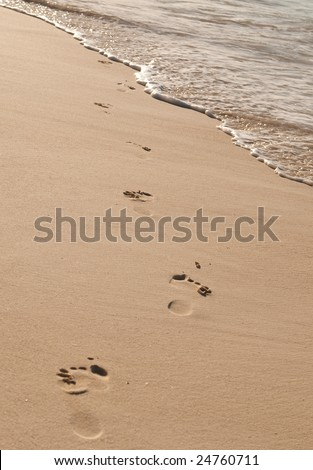Footprints on a tropical beach with the sea lapping - stock photo