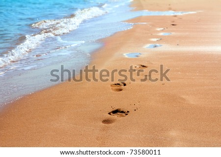 footprints on sand beach along the edge of sea - stock photo