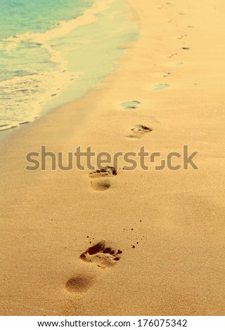 footprints on sand beach along the edge of sea - vintage retro style  - stock photo