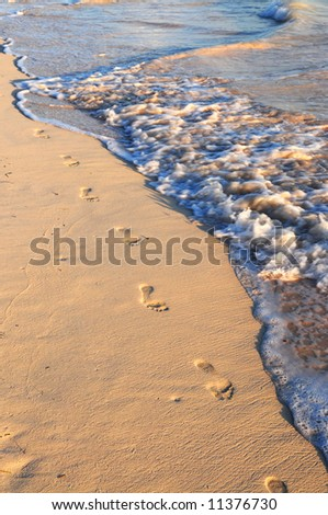 Footprints on sandy tropical beach washed away by waves - stock photo