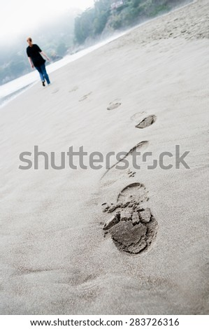 footprints on the beach sand on cloudy day and young woman walking on background - stock photo