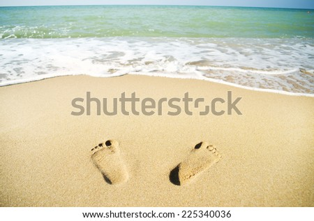 Footprints on the beach sand.Traces on the beach. - stock photo