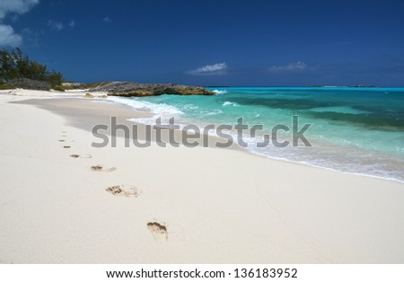 Footprints on the desrt beach of Little Exuma, Bahamas - stock photo