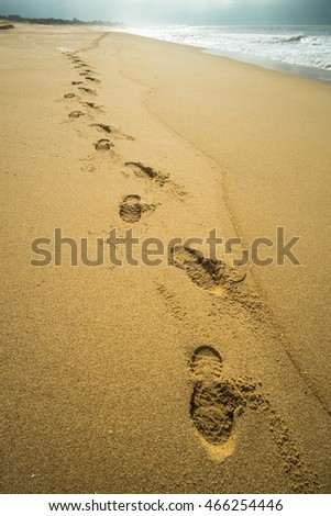Footprints on the sand of a stormy beach