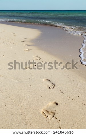 footprints on white sand beach along the edge of sea - stock photo