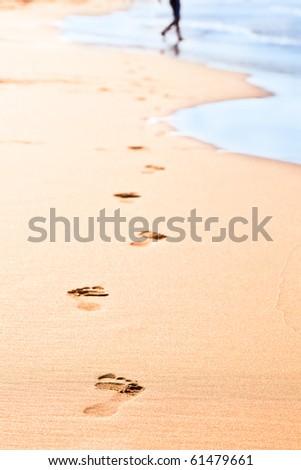 Footprints on yellow sand on the seashore - stock photo