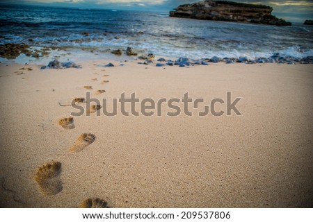 Footsteps in the crisp sand - stock photo