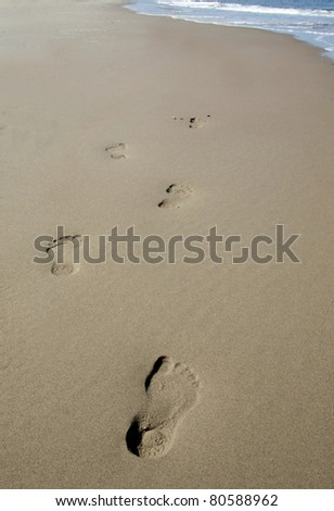 Footsteps in the sand - stock photo
