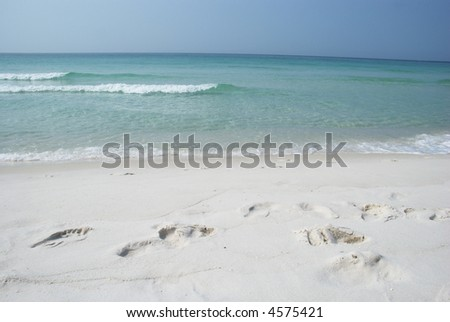 Footsteps in white sand on beach - stock photo