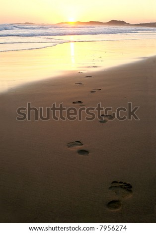 Footsteps into the sunset - stock photo
