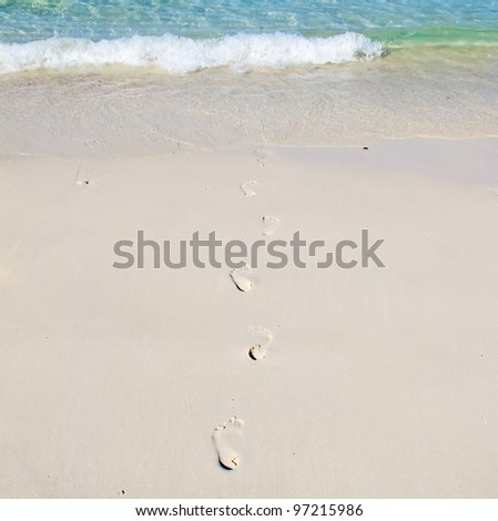 Footsteps on a white sand beach disappearing in the sea - stock photo