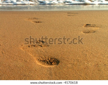 Footsteps on beach - stock photo