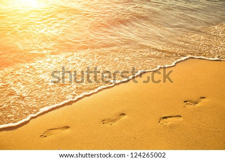 Footsteps on the beach by the sea in summer - stock photo