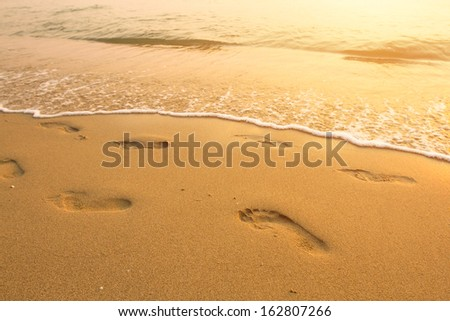 Footsteps on the beach by the sea in summer. - stock photo