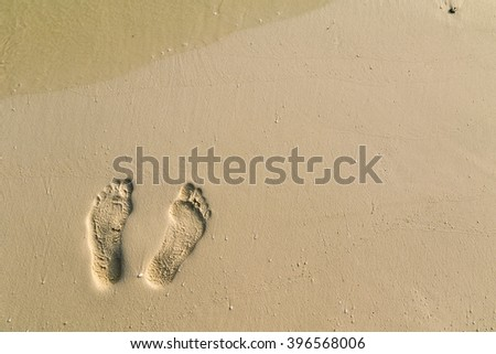 Footsteps on the coral sandy beach - stock photo
