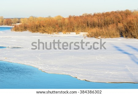 Footsteps on the ice in the shade of a forest background. - stock photo