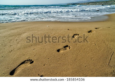 Footsteps on the sand beach - stock photo