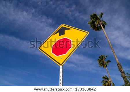 For California stop ahead. Stop sign ahead sign in the Southern California sun with palm trees in the background. - stock photo