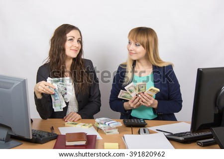 for office table two women collaborators happily hand-held fan of bundles of money, and discuss them dreamily - stock photo