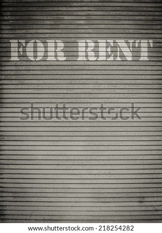For Rent Sign On Dirty Scratched Store Roller Shutters - stock photo