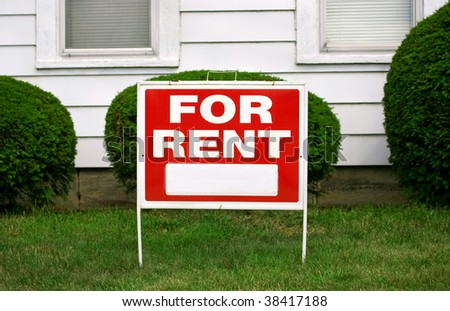 FOR RENT sign with house behind it, copy space on sign - stock photo