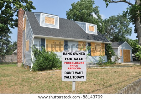 For Sale Bank Owned Real Estate Sign on Boarded Suburban Cape Cod Style Home in Residential Neighborhood - stock photo