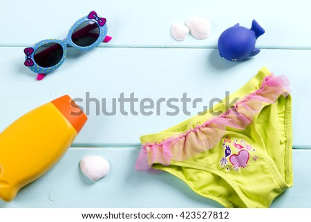 for sea accessories - sunglasses, sun lotion, a toy whale swimsuit. child. kid. sea tour - stock photo