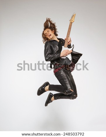 For those who know how to rock. Full-length image of handsome young guitar player in leather suit jumping with the guitar and singing isolated on grey background - stock photo