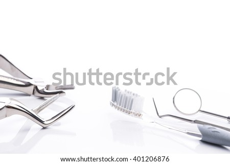 Forceps, toothbrush, dental floss, mouth mirror and dental probe on white surface