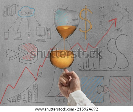 forefinger balancing sand clock on doodles wall background - stock photo