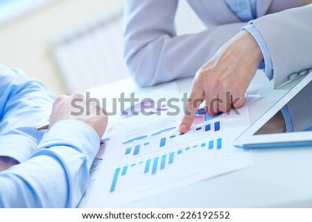 Forefinger of businesswoman pointing at chart during presentation of marketing analysis - stock photo