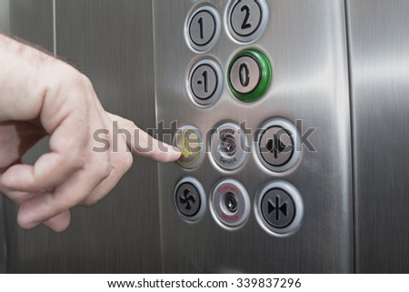 Forefinger pressing the alarm button in the elevator - stock photo
