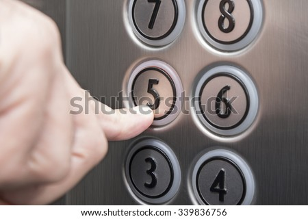 Forefinger pressing the fifth floor button in the elevator - stock photo