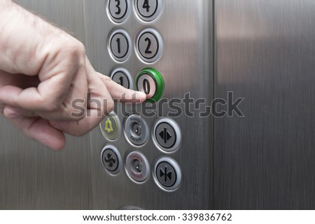 Forefinger pressing the zero floor button in the elevator - stock photo