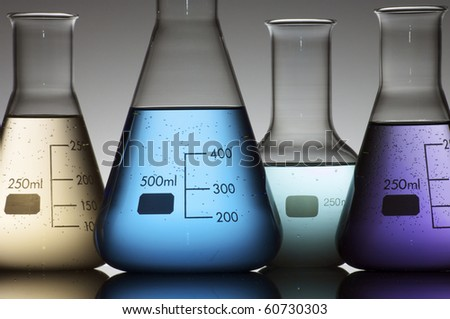forefront of a chemical laboratory flasks containing liquid shiny - stock photo