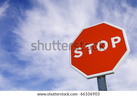 forefront of a stop sign with a cloudy sky